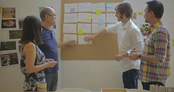 Work colleagues standing around a storyboard in different coloured clothing