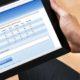 Business man completing online survey on black tablet. Survey form is blue on white background