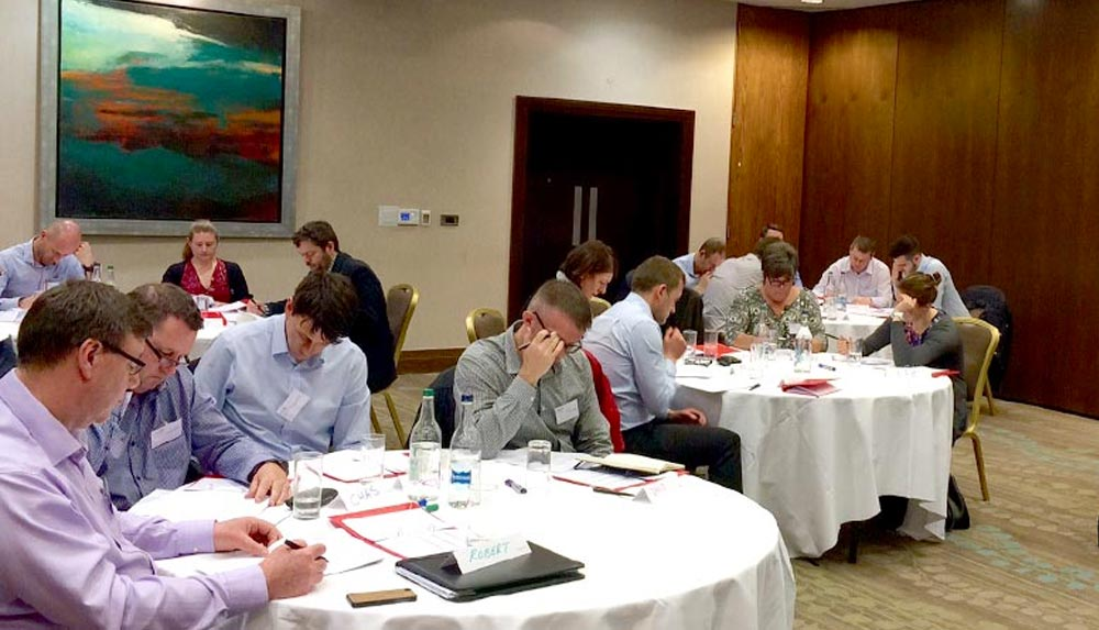 Delegates are seated at small round tables on the business strategy course