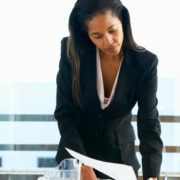 Woman dressed in dark suit working with female colleagues